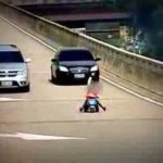 Eight-year-old rides his tricycle on the highway