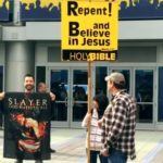 "Slayer's ""God Hates Us All"" Fahne neben religiösen Demonstranten"