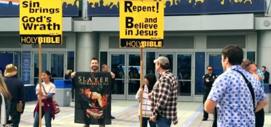 "Slayer's ""God Hates Us All"" Bandeira ao lado de manifestantes religiosos"