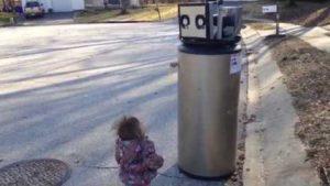 Liten jente som holder gamle varmtvannsbereder for en robot og bekjenner sin kjærlighet
